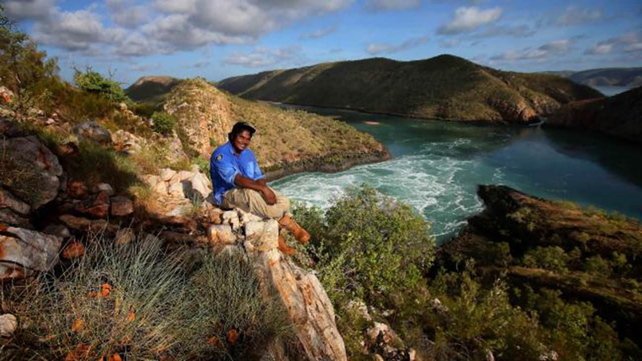 This image shows Kieran Bangmorra sitting on a hill overlooking the Horizontal Falls near Derby in Australia's northwest.