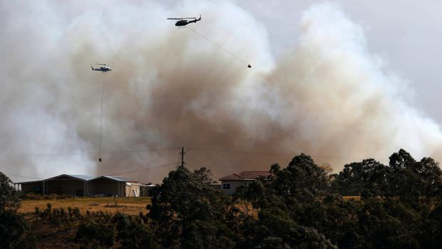 A water bombing helicopter fights the bushfire at Richmond Vale near Cessnock. Photo: AAP