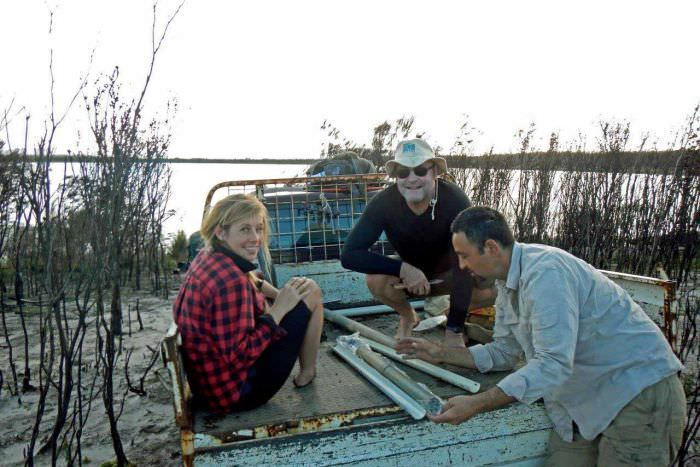 PHOTO: Researchers (left to right) Aine Nicholson, ANU professor Simon Haberle and Andry Sculthorpe inspect a core sample. (Supplied: David Bowman)