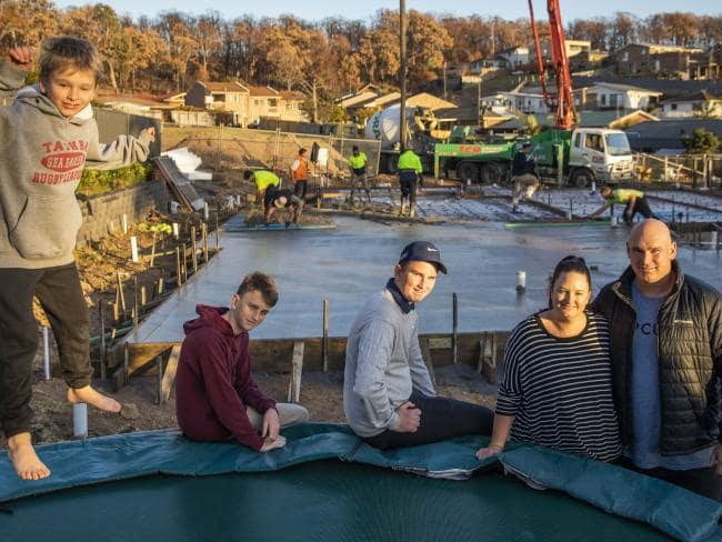 The Creary family stand on their block of land on Flora Place in Tathra as concrete is poured in the process of rebuilding their home. From left: Chad, 7, Brock, 14, Duke, 15, Alexis and Mitch. Picture: Sean Davey
